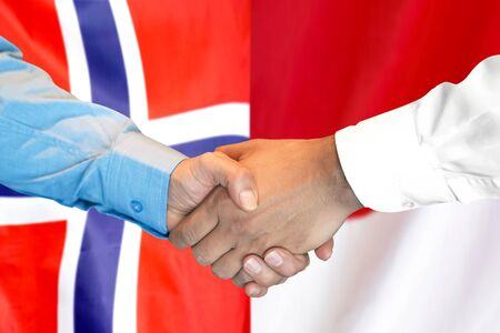 Business handshake on the background of two flags. Men handshake on the background of the Norway and Monaco flag. Support concept