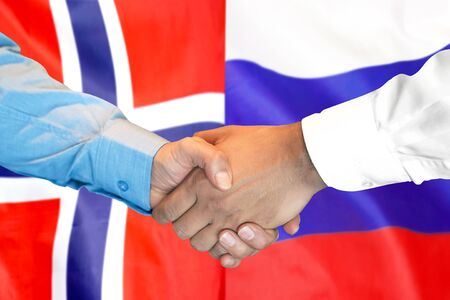 Business handshake on the background of two flags. Men handshake on the background of the Norway and Russia flag. Support concept