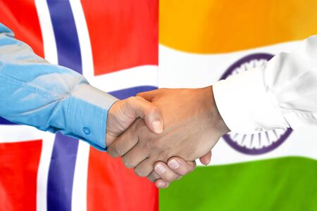 Business handshake on the background of two flags. Men handshake on the background of the Norway and India flag. Support concept Banco de Imagens