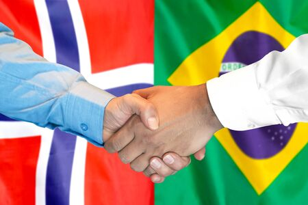 Business handshake on the background of two flags. Men handshake on the background of the Norway and Brazil flag. Support concept