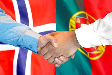 Business handshake on the background of two flags. Men handshake on the background of the Norway and Portugal flag. Support concept Banco de Imagens
