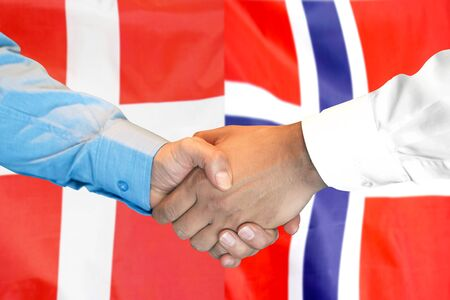 Business handshake on the background of two flags. Men handshake on the background of the Norway and Denmark flag. Support concept