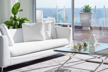 Interno del soggiorno dell'hotel. Bel soggiorno con divano bianco. White Concept Living Room Interior. Interiore moderno della camera da letto in villa di lusso. Colori bianchi, grande finestra