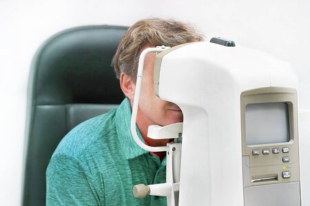A man checks eyesight in a clinician oculist. Man checks his vision on the machine checking patient vision at eye clinic or optics store. Male patient to check vision in ophthalmological clinic