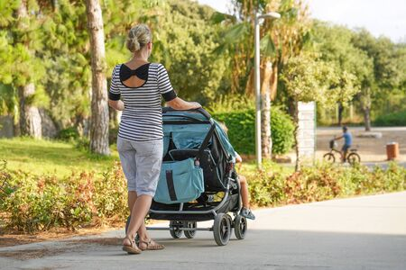 A girl with a baby carriage for two children walks in the park on a summer morning. Young mom with baby carriage. Walking. Back view Stock Photo - 132111997