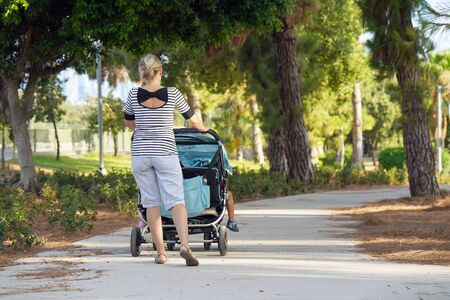 A girl with a baby carriage for two children walks in the park on a summer morning. Young mom with baby carriage. Walking. Back view Stock Photo - 132111984