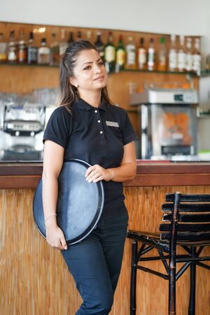Portrait of waitress standing near the restaurant bar of the hotel. A waitress with a tray is waiting for the order. Shelves with bottles of alcohol in the background. The concept of service.