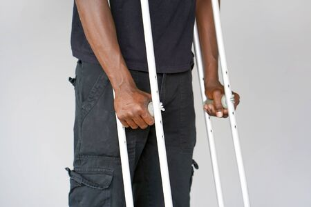 African man on crutches on a gray background. Close-up man walking with crutches. Reklamní fotografie - 132112169