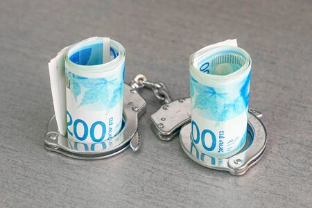 roll Israeli money bills of 200 shekel in handcuffs isolated on gray background. Shekel banknotes with handcuffs. Handcuffs and money on table. Financial crime, dirty money and corruption concept. Archivio Fotografico - 128108864