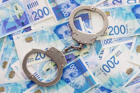 Handcuffs on the background of Israeli money. The new Israeli money bills (banknotes) of 200 shekel. Police handcuffs. Financial crime, dirty money and corruption concept.