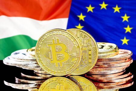 Concept for investors in cryptocurrency and Blockchain technology in the Hungary and European Union. Bitcoins on the background of the flag Hungary and European Union.