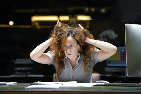 Close-up of office worker is distressed with a lot of paperwork in front of her. Close-up of an state institution worker. A lot of paper work in office. Yelling and screaming for bad results.