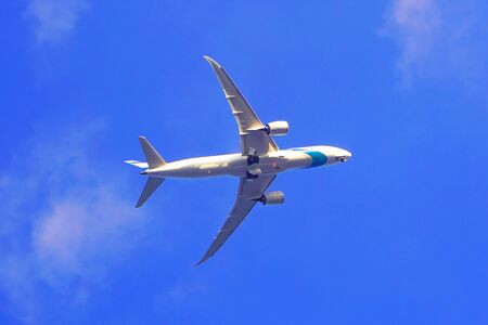 Airplane flys in the cloudy blue sky in background.