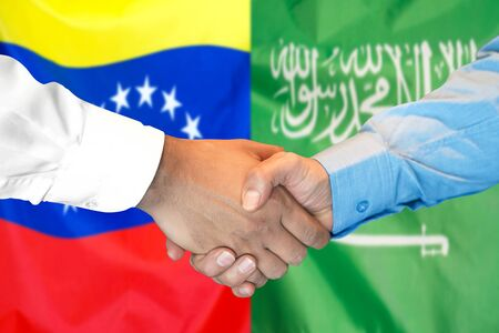 Business handshake on the background of two flags. Men handshake on the background of the Venezuela and Saudi Arabia flag. Support concept