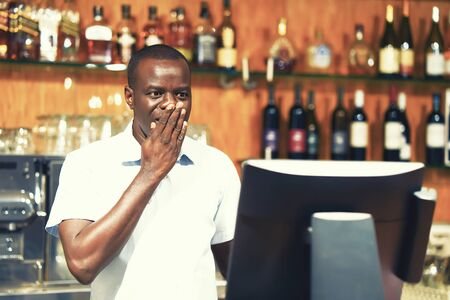 African bartender made a mistake in the bill, emotionA restaurant worker registrating new order by cash register. The concept of service.