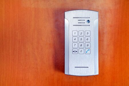 Secure password on keyboard for opening home house door on red wooden background. Password code Security keypad system protected in Public Building. The security code combination to unlock the door