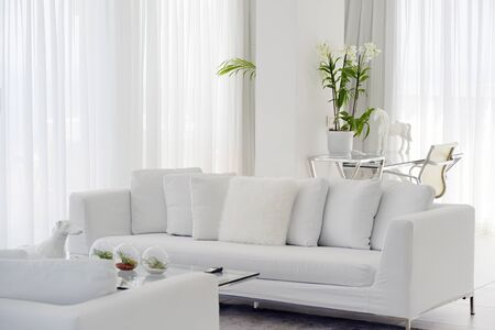 Interior of the living room of the hotel. Beautiful living room with white sofa. White Concept Living Room Interior. Modern bed room interior in Luxury villa. White colours, big window