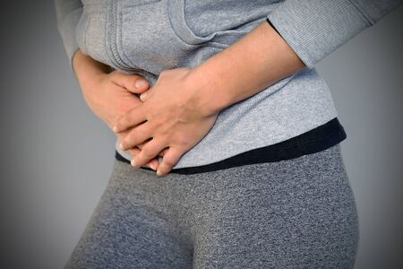 Woman having painful stomachache isolated on gray background. Chronic gastritis.