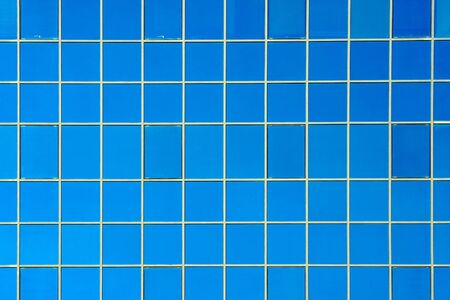 Windows of a building texture. Glass blue square windows of facade modern city business building skyscraper. Modern apartment buildings in new neighborhood.