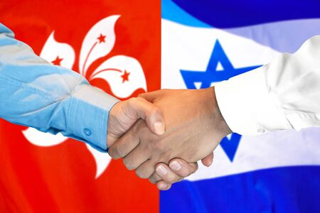 Business handshake on the background of two flags. Men handshake on the background of the Hong Kong and Israel flag. Support concept Banco de Imagens