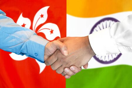 Business handshake on the background of two flags. Men handshake on the background of the Hong Kong and India flag. Support concept Banco de Imagens