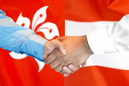 Business handshake on the background of two flags. Men handshake on the background of the Hong Kong and Austria flag. Support concept