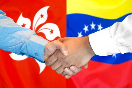Business handshake on the background of two flags. Men handshake on the background of the Hong Kong and Venezuela flag. Support concept