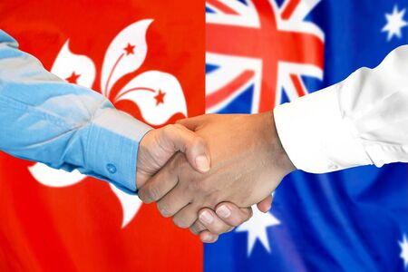 Business handshake on the background of two flags. Men handshake on the background of the Hong Kong and Australia flag. Support concept