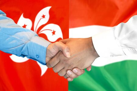 Business handshake on the background of two flags. Men handshake on the background of the Hong Kong and Hungary flag. Support concept