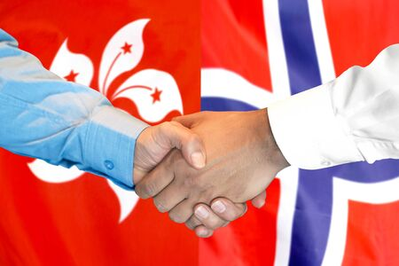 Business handshake on the background of two flags. Men handshake on the background of the Hong Kong and Norway flag. Support concept 스톡 콘텐츠