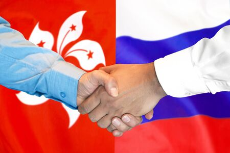 Business handshake on the background of two flags. Men handshake on the background of the Hong Kong and Russia flag. Support concept Banco de Imagens