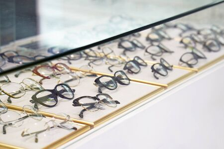 Stand with glasses in the store of optics, eye concept. Close-up many glasses on a stand. Banco de Imagens