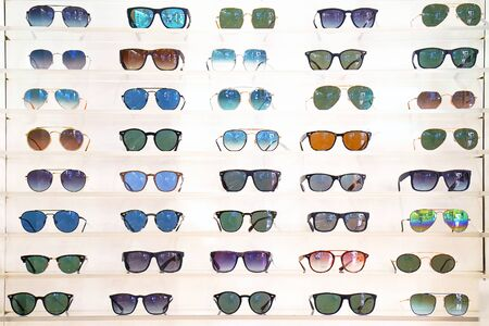 Stand with sunglasses. Sale the city market or in the store sunglasses. Trendy sunglasses, Summer eyeglasses, fashion collection, Different sunglasses on a stand. Banco de Imagens