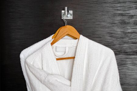 Two white coats hanging on the door. Hotel dressing gowns on the door hanger.