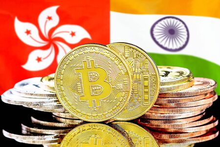 Concept for investors in cryptocurrency and Blockchain technology in the Hong Kong and India. Bitcoins on the background of the flag Hong Kong and India.