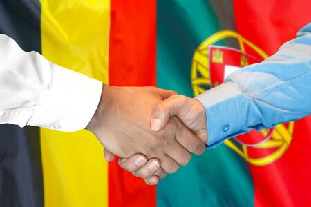 Business handshake on the background of two flags. Men handshake on the background of the Belgium and Portugal flag. Support concept Stock fotó