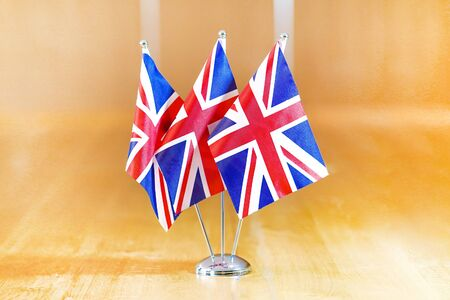 Three flags on the table. Flags of United Kingdom. Flags of United Kingdom on the table during a meeting of foreign ministers of UK.