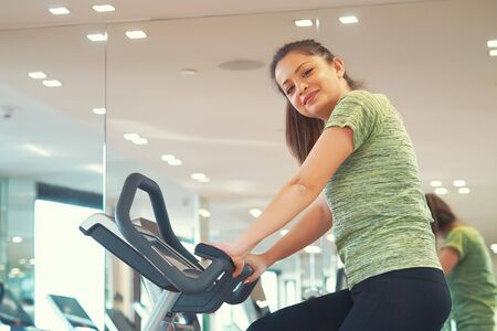 Woman runs on a treadmill, is engaged in fitness sport club. Young girl in gym. Healthy lifestyle, gymnastics, weightloss concept.