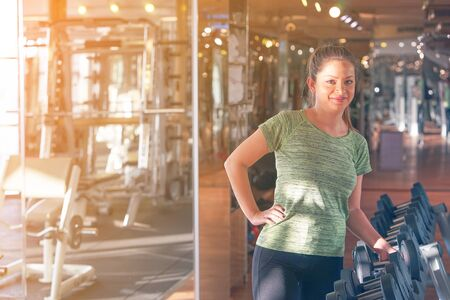 Woman takes dumbbells out of a row at the gym. Looking at camera and smiling. The concept of health and weight loss. Toning.