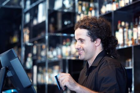 Bartender registration of a new order by a cash register. The barman pays the order with a credit card. Service concept. Banco de Imagens