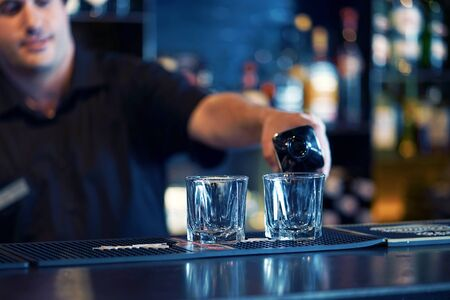Bartender man pours whiskey to the client of the hotel bar. The concept of service. Focus on the bartender. Toning.