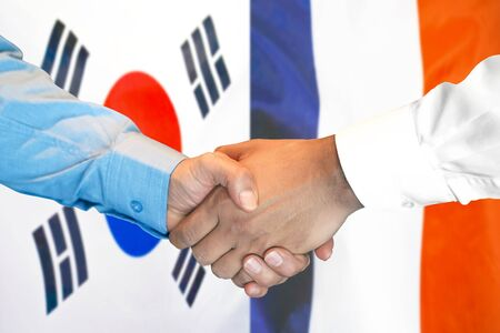 Business handshake on the background of two flags. Men handshake on the background of the South Korea and France flag. Support concept