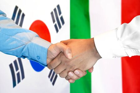 Business handshake on the background of two flags. Men handshake on the background of the South Korea and Italy flag. Support concept