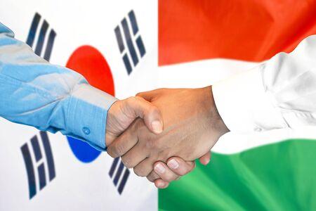 Business handshake on the background of two flags. Men handshake on the background of the South Korea and Hungary flag. Support concept Stok Fotoğraf