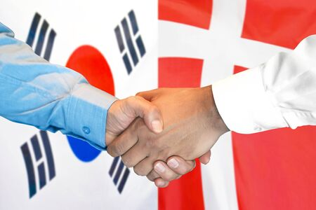 Business handshake on the background of two flags. Men handshake on the background of the South Korea and Denmark flag. Support concept