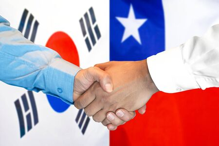 Business handshake on the background of two flags. Men handshake on the background of the South Korea and Chile flag. Support concept Stok Fotoğraf