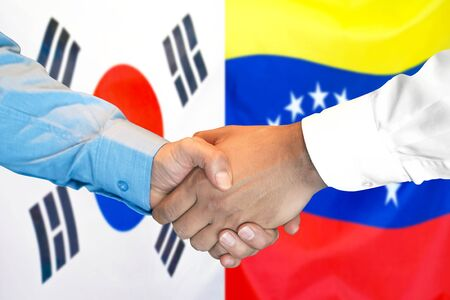 Business handshake on the background of two flags. Men handshake on the background of the South Korea and Venezuela flag. Support concept