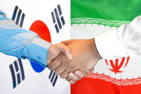 Business handshake on the background of two flags. Men handshake on the background of the South Korea and Iran flag. Support concept