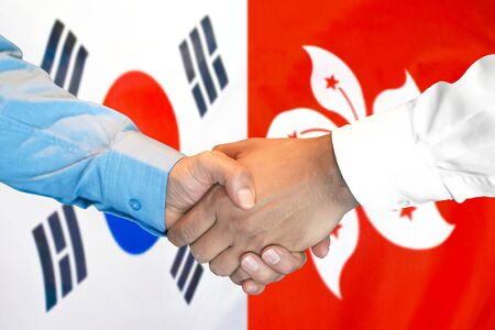 Business handshake on the background of two flags. Men handshake on the background of the South Korea and Hong Kong flag. Support concept Stok Fotoğraf