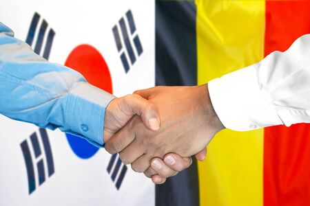 Business handshake on the background of two flags. Men handshake on the background of the South Korea and Belgium flag. Support concept Stok Fotoğraf